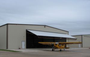 Aircraft hangar and Piper Cub airplane, photo credit wikiWings